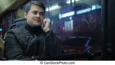 Man Talking on the Phone in Bus - Young man is sitting in...