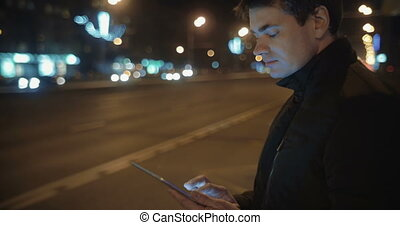 Man Writing Letters in Tablet PC while Waiting for the Bus -...