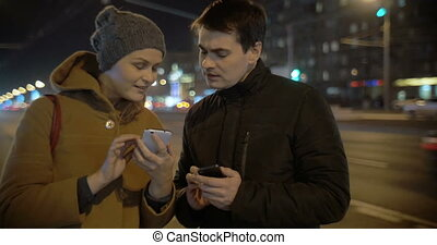 Friends with Smartphones - Two friends are standing by the...