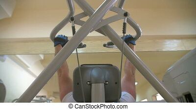 Exercises on Weight-Lifting Machine - Man is lifting weight...