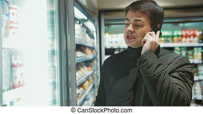 Man Talking on the Phone in Food Store - Shot of a man in a...
