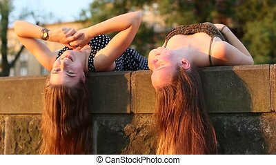 Two young girls lying and talking on a stone slab with long...