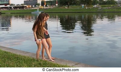 Two teenage girls walking along the city waterfront during...