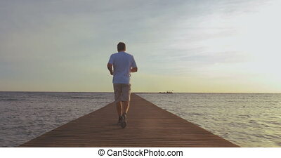 Man jogging on the pier at sunset - Steadicam back shot of a...