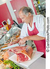 Man cutting raw meat