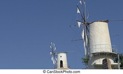 Two old white windmills working