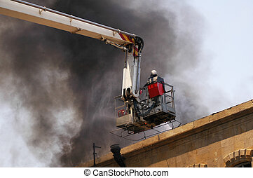 Firefighter on the firetruck boom during fire - Firefighter...