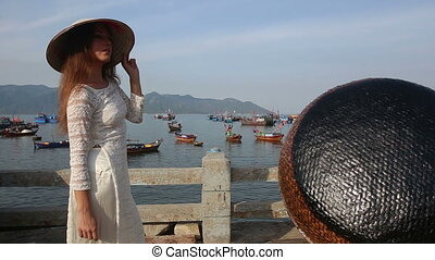 girl poses in vietnamese hat on embankment - european girl...