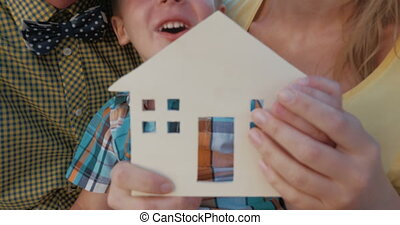 Real estate concept with happy family and small wooden house