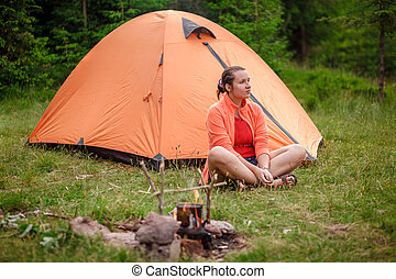 The woman at a fire with a tent
