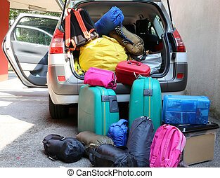trunk of a car overloaded with suitcases for family travel -...