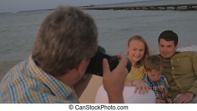 Taking pictures of the family on sea shore - Photographer...