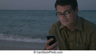 Man Using Smartphone by the Sea - Young man is sitting by...