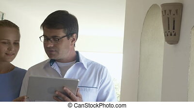 Doctor with tablet talking to female patient - Steadicam...