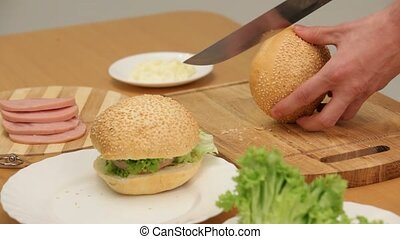 Delicious Food - A man prepares a delicious sandwich with...