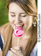 cute girl enjoying licking red twisted lollipop - Portrait...