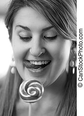 Black and white portrait of woman looking at lollipop
