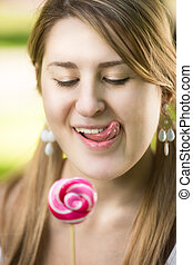portrait of cute woman with pigtails looking at red lollipop...