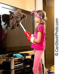 girl in rubber gloves cleaning big TV from dust with brush -...