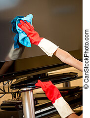 Closeup of woman in rubber gloves cleaning TV screen with...
