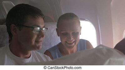 Young couple making selfie with cell in plane - Happy young...