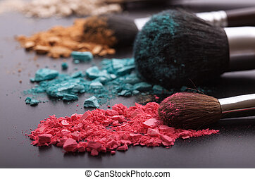 Makeup brushes on background with colorful powder. Crushed...