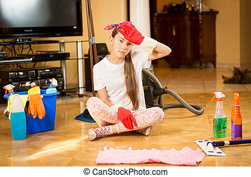 Tired teen girl sitting on floor after cleaning living room...