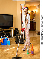 teenage girl cleaning floor at living room with vacuum cleaner