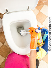 Closeup of woman in rubber gloves cleaning toilet with brush...