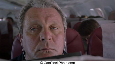 Sleepy man listening to music in airplane - Close-up shot of...