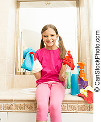 happy smiling girl in rubber gloves posing with rag at bathroom