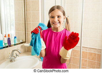portrait of cute girl in rubber gloves doing cleanup at...