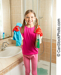 girl in rubber gloves cleaning bathroom with cloth and spray...