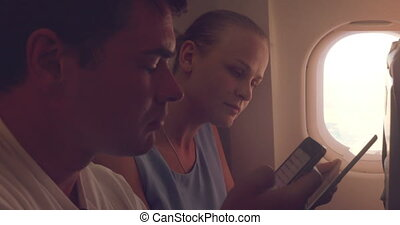 Young people using tablet PC and cell phone in plane