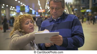 Senior couple with touch pad at the airport - Senior woman...
