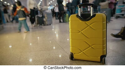 Yellow suitcase on the floor at crowded airport
