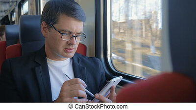 Young man using cell to browse online in train - Young...