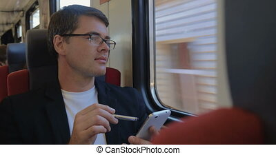 Man with cell phone enjoying view from the train window
