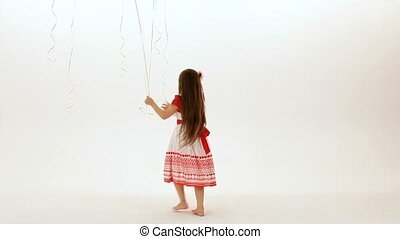 Collect All The Balloons - A little girl runs happily on a...