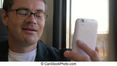Man having a video chat on mobile during train ride -...