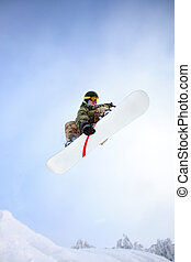 Snowboarder jumping through air with blue sky.