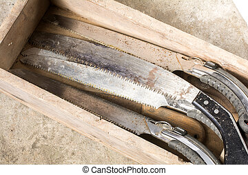 Worn out saws in the wooden box