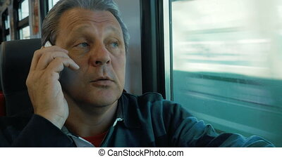 Man Answering the Phone - Mature man is traveling by train....