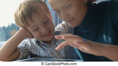 Mother and son playing game on pad in train - Young mother...