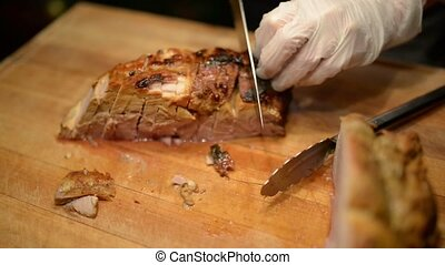 Closeup of roast meat is carved by a chef
