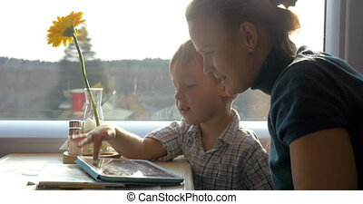 They passing time with touch pad in the journey - Mother and...