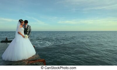 Romantic Moment - Newlyweds standing on the dock throwing...