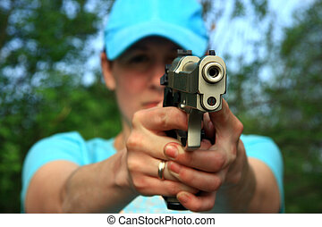 woman with gun aims