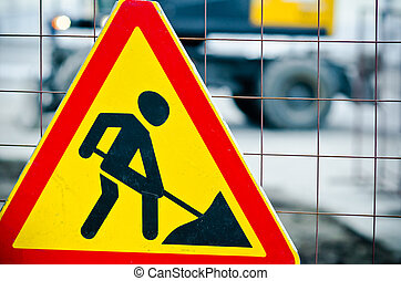 Road works sign hanging on a fence close up