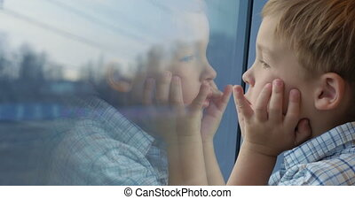 Boy looking out the train window with hands on the fac